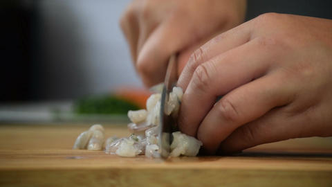 Close-up of professional chefs hand using knife to finely chop raw prawns Footage
