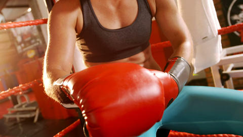 Female boxer wearing boxing gloves in fitness studio Live Action