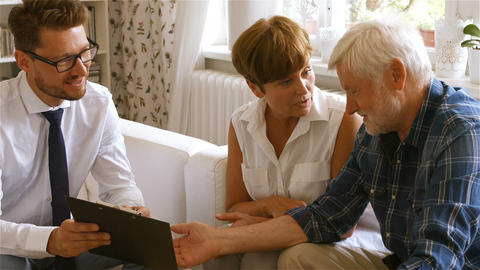 Senior couple planning their investments with financial advisor Footage