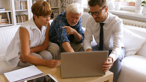 Senior couple planning their investments with financial advisor on laptop Footage