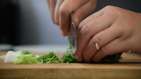 Chopping spring onion & coriander for cooking Footage
