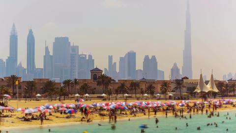 Tilt-shift timelapse of tourist people enjoy public beach on city skyline backgr Footage