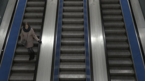 Girl moves downstairs on escalator view from above Footage