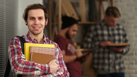 Smiling hipster student holding books at library Footage