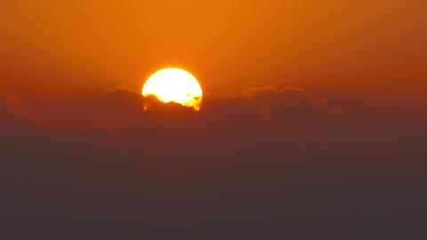sun rising between clouds, telephoto lens, 4k Footage