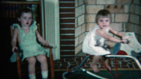 1960: Young girl sisters playing with rocking chairs and toy horses in front of  Footage