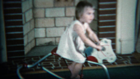 1960: Girl riding toy horse in front of the living room fireplace Footage