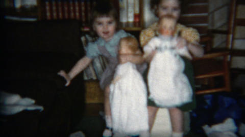 1960: Girls showing off their large baby dolls inside the cozy house Footage