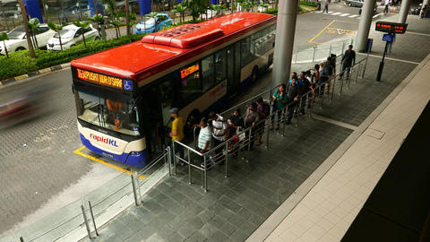 People queue walk into public bus, depart from terminal station, time lapse Footage