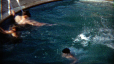 1960: Hotel diving board by a band of kids jumping head first into the water Footage