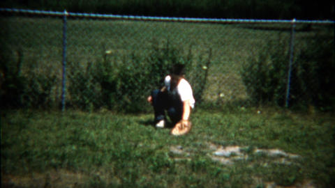 1960: Boy windup pitching baseball to friend catching against house Footage
