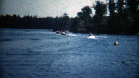 1960: Kid waterskiing lets go and sinks down in front of the dock Footage