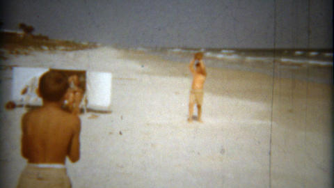 1960: Boys playing baseball catch on the ocean beach waved background Footage