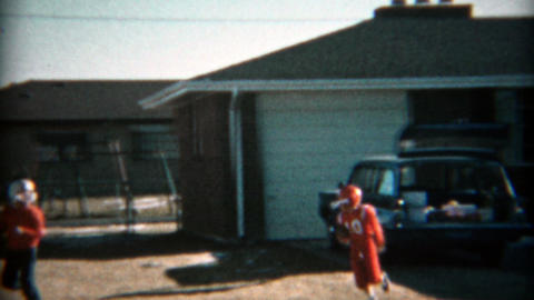 1957: Kids practicing tackle football in the front yard with helmets and uniform Footage