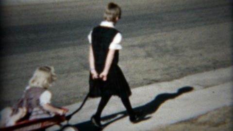 1957: Girl pulled around in red wagon on the new suburban sidewalk Footage