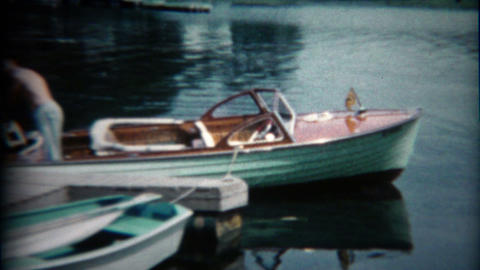 1960: Dad and son fixing family wooden boat motor propeller Footage