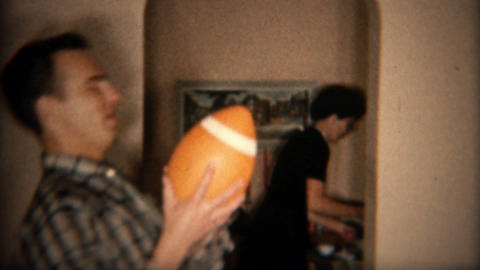 1957: Handsome father surprised by toy football thrown in house Footage