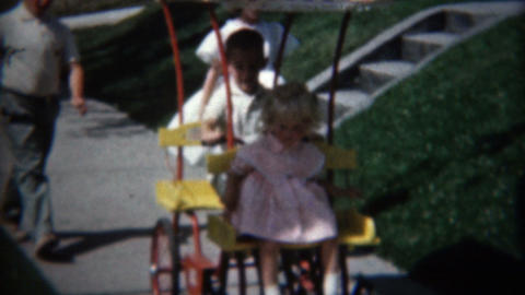 1957: Kids playing on the sidewalk with old tyme cover peddle cart Footage