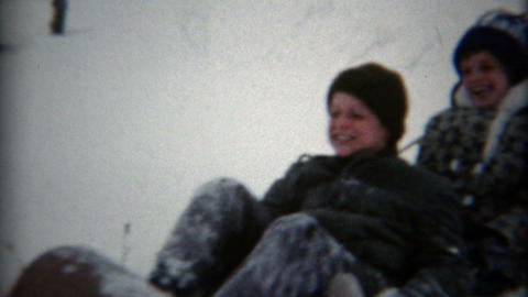 1957: Family sledding in a toboggan on a gentle slope in deep snow Footage