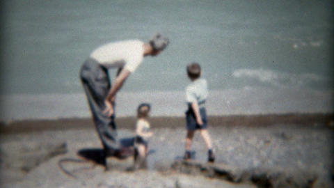 1955: Family with boys playing at lakeshore seawall beach Footage