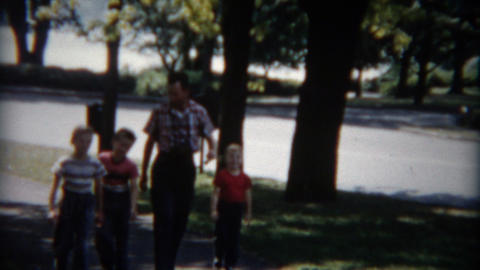 1955: Proud dad walking with 3 sons in tow on a sunny summer day Footage