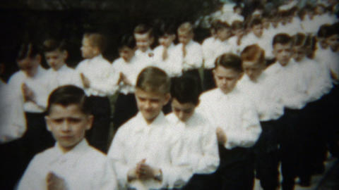 1954: Bashful boys 1st catholic communion walk led by nuns and priests Footage