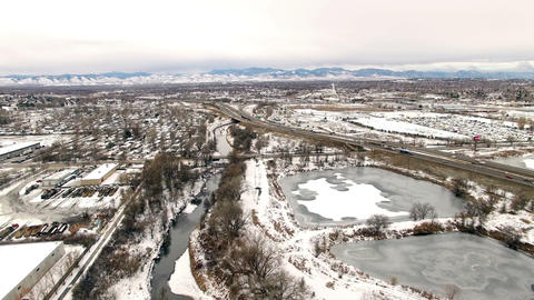 Aerial drone pan left winter gray mountain range industrial park residential Footage