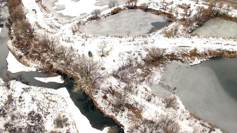 Aerial drone tilt up to frozen highway ponds winter overcast cloudy mountain ran Footage