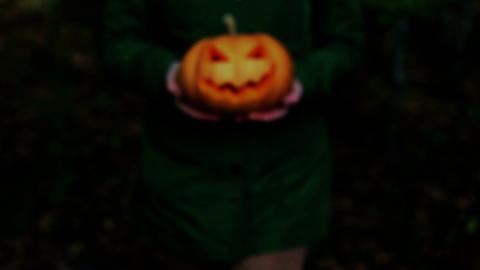 Woman carrying on hands terrible pumpkin Jack o Lantern Footage