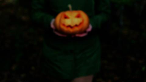 Woman carrying on hands terrible pumpkin Jack o Lantern Footage