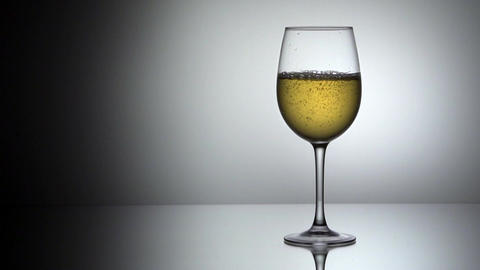 Pouring white wine into glass, slow motion Footage