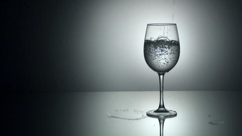 Pouring water into glass, slow motion Footage
