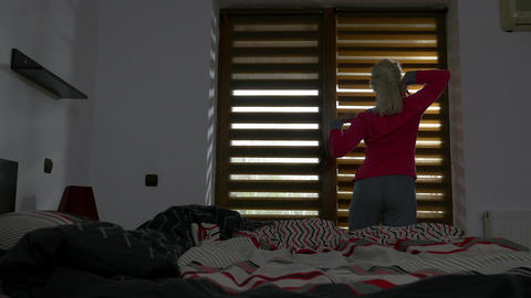 Beautiful girl gets out of bed and starts morning exercise by the window Footage