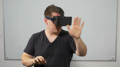 Guy experiencing video game in virtual reality with special equipment headset Live Action