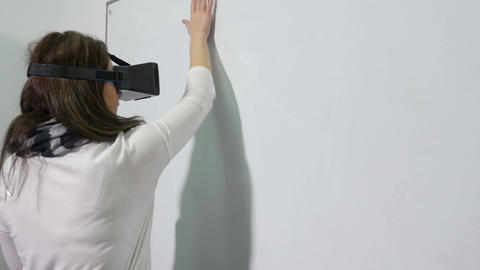 Woman enters virtual reality world using VR glasses and writes on interactive wh Footage