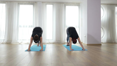 Two women doing yoga sequence Footage