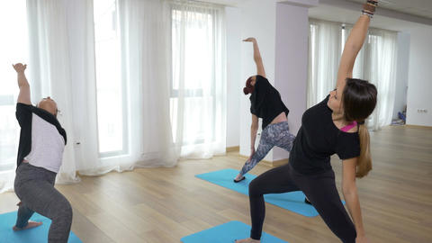Two learners practicing yoga sequence with teacher guiding them Footage