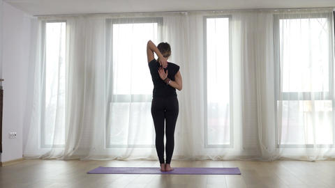 Yogi doing yoga exercise at the gym facing the sunlight in front of the window Footage