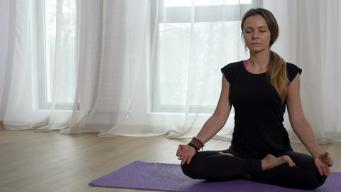 Woman meditating in lotus pose in a yoga studio Footage