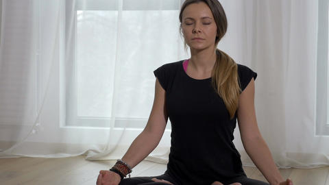 Beautiful adult female meditating in lotus pose in a yoga gym Footage