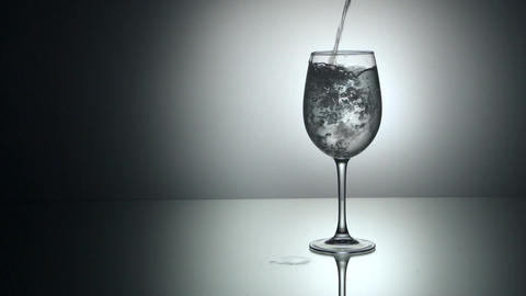 ouring water into glass with ice cubes, slow motion Footage