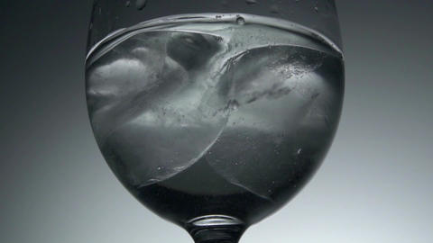 Pouring water into glass with ice cubes, slow motion Footage