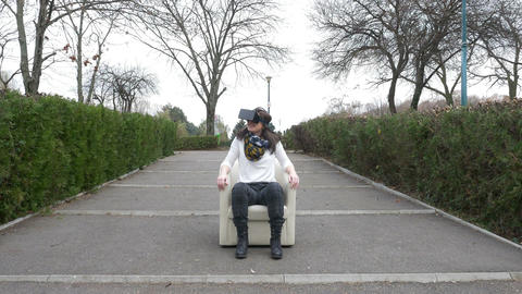Woman uses VR equipment while relaxing in an armchair in a park Footage