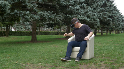 Man sitting in an armchair in the park looking at surroundings with virtual real Footage