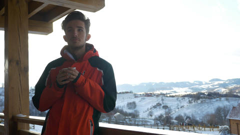 Young man drinking a cup of hot coffee on a deck in winter time Footage