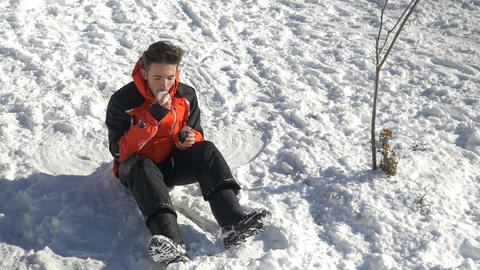 Teenager laying down in the snow making a snowball and eating snow Footage