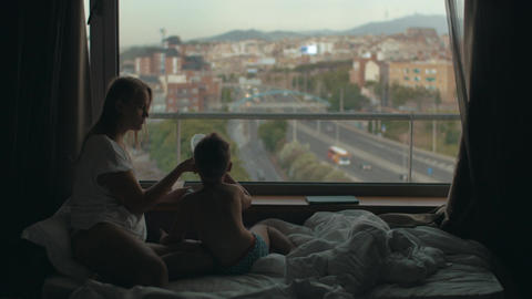 View of mother lying on the bed with small son against huge panoramic window and Live Action