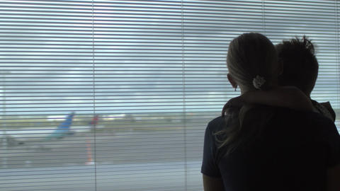 Child and mother looking at airplanes through window Footage