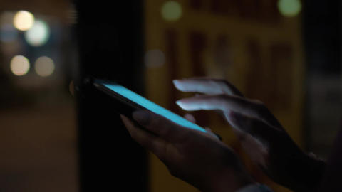Woman typing on cellphone walking in night city Footage