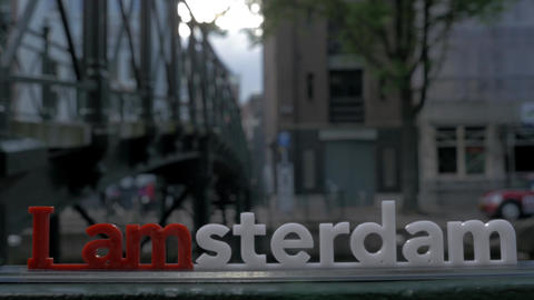 View of small plastic figure of Iamsterdam letters sculpture on the bridge Footage
